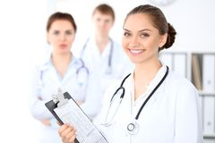Happy female doctor keeping medical clipboard while medical staff are at the background Royalty Free Stock Photography