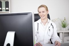 Happy Female Doctor Looking at her Computer Screen Royalty Free Stock Photo