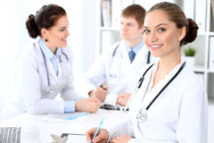 Happy female doctor and medical staff discussing something while sitting at the table Stock Images