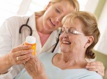 Female Doctor or Nurse Explaining Prescription to Senior Adult W Royalty Free Stock Photos