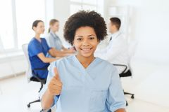 Happy female doctor or nurse showing thumbs up Stock Photos