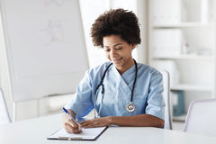 Happy female doctor or nurse writing to clipboard Royalty Free Stock Image