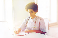 Happy female doctor or nurse writing to clipboard Stock Photos