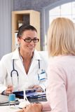 Happy female doctor at office with patient Royalty Free Stock Photo