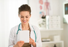 Happy female doctor in the office using tablet PC Stock Image
