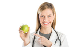 Happy Female Doctor Pointing At Green Apple Stock Image