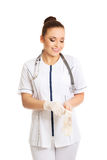 Happy female doctor putting on protective gloves Stock Photos