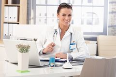 Happy female doctor sitting at medical office desk. Happy brunette caucasian female doctor sitting at medical office desk in front of laptop computer, wearing stock photo