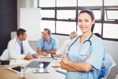 Happy female doctor standing with arms crossed in conference room Stock Photo