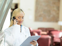 Happy female doctor talking to a patient on a phone Stock Photos