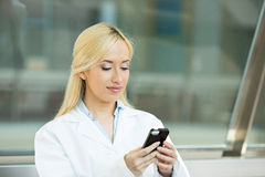 Happy female doctor texting on smart phone Royalty Free Stock Photography