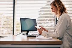 Female doctor using her digital tablet in the consultation royalty free stock images