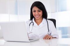 Happy female doctor using laptop Stock Photo
