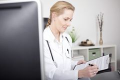Happy Female Doctor Writing Diagnosis on a Paper Royalty Free Stock Photo