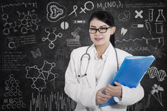 Happy female doctor with written blackboard Stock Photo