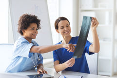 Happy female doctors with x-ray image at hospital. Radiology, surgery, people and medicine concept - happy female doctors looking to and discussing x-ray image Royalty Free Stock Photo