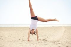 Happy Female Doing Cartwheel on the Beach Royalty Free Stock Photography