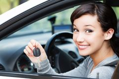 Happy female driver showing car key. Closeup shot of happy female driver showing car key royalty free stock photo