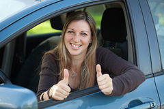 Happy female driver showing thumbs up Stock Photos