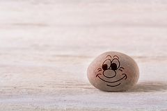Happy female emoticon. Stone face on white wood background with free space for your text Royalty Free Stock Photos