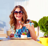Happy female enjoys sweet cake in cafe Royalty Free Stock Photo