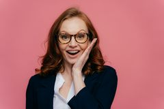 Happy female entreprenuer touches cheek gently, smiles broadly, wears transparent glasses, has ginger hair, dressed in formal stock photo