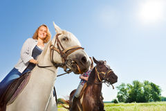 Happy female equestrians riding beautiful horses. Close-up portrait of two happy female equestrians riding beautiful purebred horses at flowery meadows Stock Photography