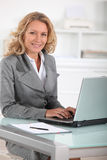 Happy female executive at her desk Royalty Free Stock Images