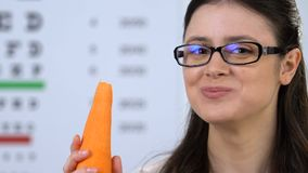 Happy female in eyeglasses eating carrot, fresh vitamins for eyes care, carotene. Stock footage stock footage