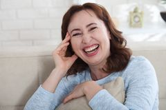 Happy female face. Attractive and beautiful middle aged woman sitting on sofa . stock image
