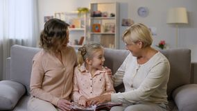 Happy female family members watching photo album pictures, having fun together. Stock footage stock footage