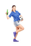 Happy female fan holding a football and beer Royalty Free Stock Photo