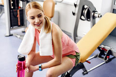 Happy female feeling weariness in gym. Outgoing girl feeling fatigue after good workout in gym. She keeping blender bottle in arms while sitting on weight bench Royalty Free Stock Photography