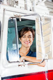 Happy Female Firefighter Sitting In Firetruck. Portrait of happy young female firefighter sitting in firetruck royalty free stock photography