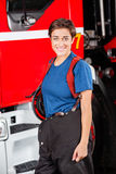 Happy Female Firefighter Standing Against. Portrait of happy female firefighter standing against firetruck at station royalty free stock images