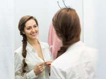 Happy female at fitting-room. Portrait of happy female with new garment at fitting-room Stock Image