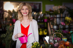 Happy female florist holding a watering can in flower shop Stock Image
