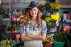 Happy female florist standing with arms crossed in flower shop Royalty Free Stock Images