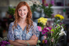 Happy female florist standing with arms crossed in flower shop Stock Images