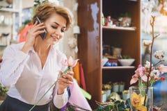 Happy female florist talking on smartphone stock photography