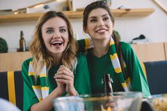 Happy female football fans in green t-shirts and scarf gesturing by hands during watch of soccer match. At home royalty free stock images