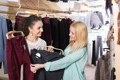 Happy female friends choosing trousers  and smiling Royalty Free Stock Photography