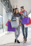 Happy female friends communicating while carrying shopping bags on sidewalk Royalty Free Stock Photography