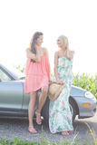 Happy female friends conversing while standing by convertible against clear sky Stock Photography