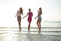 Happy female friends dancing on beach stock photos