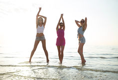 Happy female friends dancing on beach. Friendship, summer vacation, party, happiness and people concept - group of happy female friends dancing on beach royalty free stock image