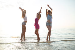 Happy female friends dancing on beach. Friendship, summer vacation, party, happiness and people concept - group of happy female friends dancing on beach royalty free stock photography