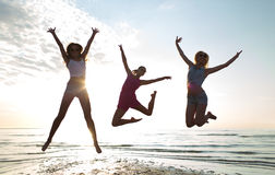 Happy female friends dancing and jumping on beach. Friendship, summer vacation, freedom, happiness and people concept - group of happy female friends dancing and Royalty Free Stock Image