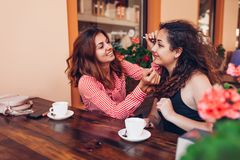 Happy female friends doing makeup while having coffee in outdoor cafe in summer. Women chatting and chilling royalty free stock photo