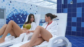 Happy female friends dressed in bathrobes and bikini relaxing at spa next to a swimming pool. Professional shot on Lumix GH4 in 4K resolution. You can use it e stock footage